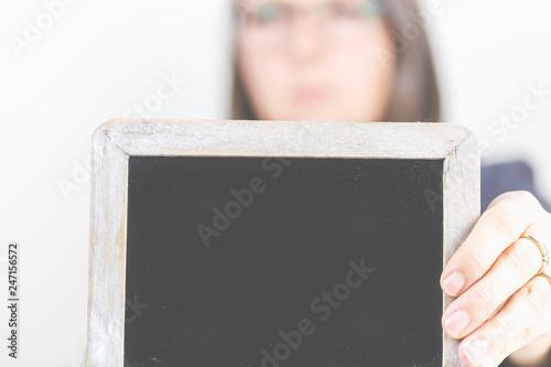 fototapeta na ścianę Eine Frau hält eine Schreibtafel in die Kamera.