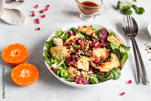 Salad mix with grilled turkey or chicken, seeds and citrus dressing on a white plate. Light concrete background. Healthy lunch or dinner. Copy space. - 247160568