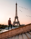 Fototapeta Paryż - Paris Eiffel tower man watching sunrise Sunrise by Eifel tower Paris © Fokke