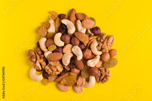 fototapeta na ścianę Nut mix in a heap. Various nuts and raisins on a yellow background.