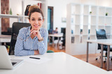 Portrait of a beautiful smiling female office worker sitting at workplace. - 247167134