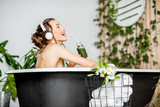 Young relaxed woman listening to the music and drinking smoothie while lying in the retro bathtub at the beautiful bathroom with green plants - 247171779
