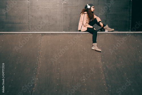 Mixed race hipster teenage girl with serious facial expression enjoying music and sitting in skate park.