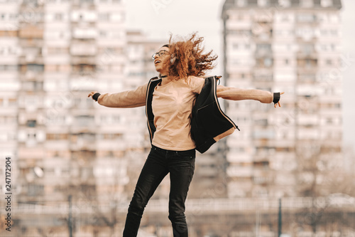 fototapeta na ścianę Beautiful mixed race hipster teenage girl with curly hair enjoying music and jumping. In background blurred buildings.