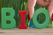 Quadro Bio word from plastic letters in front of green natural background