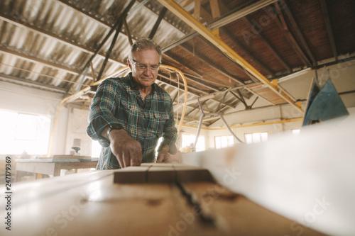 Senior male carpenter working in carpentry workshop - 247179369