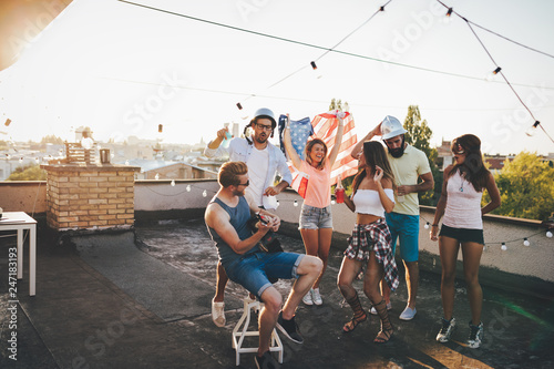 Group of happy friends having party on rooftop
