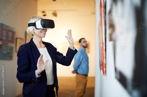 Leinwanddruck Bild Waist up portrait of contemporary smiling woman wearing VR headset in art gallery, copy space