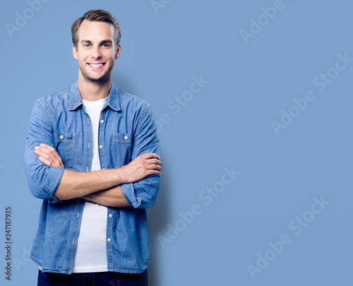 Portrait of young man standing in crossed arms pose © vgstudio