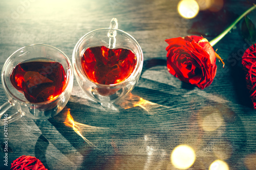 Leinwandbild Motiv St. Valentine's Day scene. Valentine heart shaped tea cups with red hearts rattan decor and red rose on wooden background. Dating