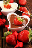 Valentine Chocolate fondue melted with fresh strawberries and dark and white chocolate. Tublips and sugar hearts. - 247194375