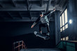 Leinwanddruck Bild - Skateboarder jumping high on mini ramp at skate park indoor.