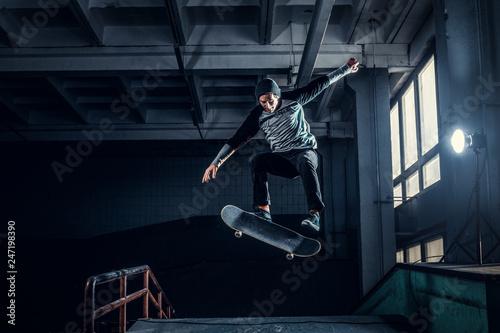 Leinwanddruck Bild Skateboarder jumping high on mini ramp at skate park indoor.