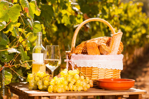 Leinwanddruck Bild glass of white wine ripe grapes and picnic basket on table in vineyard