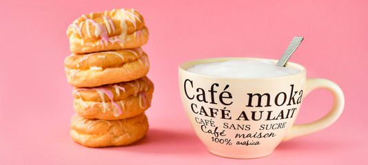 a large Cup of cappuccino coffee and a lot of with donuts, Breakfast concept, a Cup in french written mocha coffee, coffee with milk, coffee without sugar. pink background, selective focus © Elena