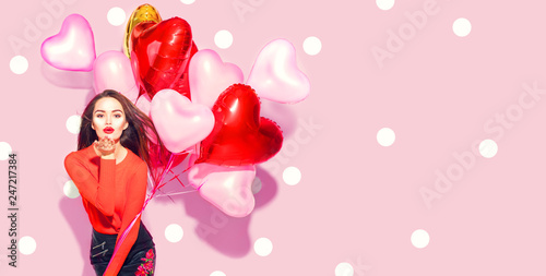 Valentine's Day. Beauty girl with colorful air balloons having fun over pink polka dots background - 247217384
