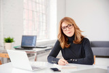 Businesswoman sitting at office desk and doing some paperwork - 247217934