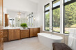 Leinwandbild Motiv Beautiful bathroom in new luxury home, with double vanity, bathtub, and shower visible in mirror reflection.