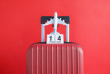 Luggage with valentines day date calendar and aircraft on red background minimalistic vacation concept. - 247224734