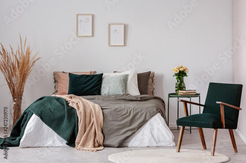 Wooden armchair next to bed and table with flowers in white simple bedroom interior. Real photo