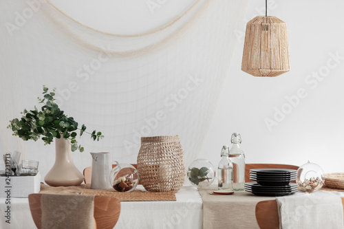 Green plant in beige vase, white jug and wicker lantern on dining table in bright interior