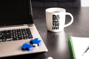 do what you love, still life with blocknote, labtop, pen and a white mug of coffee over a black office desk. symbol of job