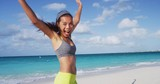 Cheerful Woman In Sportswear Cheering While Running At Beach Against Sky. Happy woman in sportswear waving ams running on sea shore against sky. Excited female jogger is at beach during summer. - 247239117