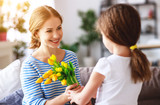 happy mother's day! child daughter gives mother a bouquet of flowers to tulip and gift