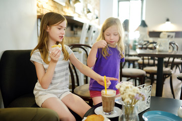 Cute young girls drinking hot chocolate and eating desserts in a cafe on hot summer day.