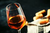 Trendy food and drink, orange wine in glass, gray table background, space for text, selective focus