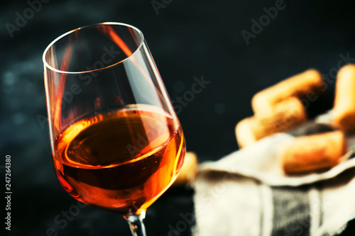 Leinwanddruck Bild Trendy food and drink, orange wine in glass, gray table background, space for text, selective focus