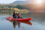 Mother and daughter rowing boat on calm waters - 247269523