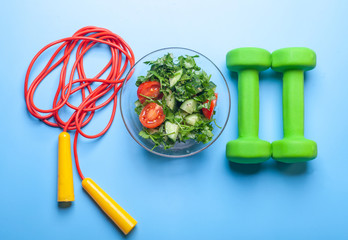 fresh salad bowl, dumbbells and jumping rope on bright blue background