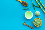 Asian spa treatment concept with natural ingredients. Spa salt, lotion, sponge near bamboo on blue background top view copy space