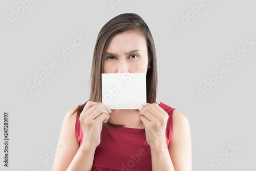 Leinwandbild Motiv A woman in the red shirt holding the blank white card with space for text in front of his mouth against the gray background