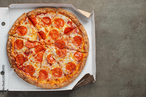 Leinwanddruck Bild Tasty pepperoni pizza in a box on brown concrete background. Top view of hot pepperoni pizza. With copy space for text. Flat lay