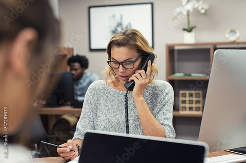 Businesswoman talking on phone at office - 247299373