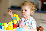 Adorable toddler girl playing with educational toys in nursery. Happy healthy child having fun with colorful different plastic blocks at home. Cute baby learning creating and building. - 247303704