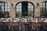in backyard of villa in Tuscany there is banquet wooden table decorated with cotton and eucalyptus compositions, glasses, candles and plates are placed on table, transparent chairs are next to them