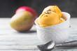 Leinwanddruck Bild - Homemade mango ice cream in a bowls with fresh fruits over white wooden background.