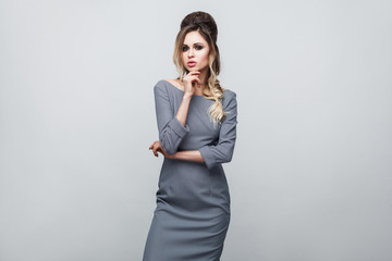 Portrait of beautiful attractive fashion model in grey dress with makeup and hairstyle standing, posing and touching her chin and looking at camera. indoor studio shot, isolated on grey background. © khosrork