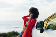 Fashionable afro hair woman on vacation calling on cell phone towards the sea. Stylish black model relaxing on a car trip to the coast.