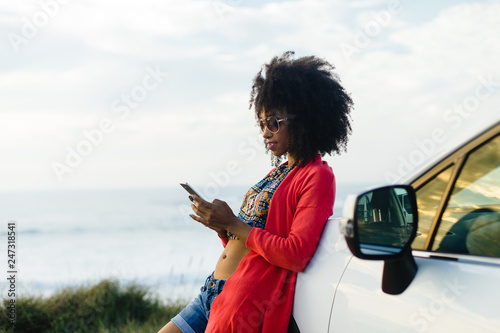 Foto Murales Fashionable afro hair woman on vacation texting on smartphone towards the sea. Stylish black model relaxing on a car trip to the coast.