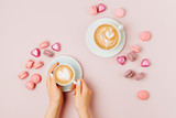 Female hands  holding cup of coffee on pale pink background.   Flat lay, top view