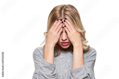 Stressed Exhausted Young Female Student Having Strong Tension Headache. Feeling Pressure And Stress. Depressed Student With Head in Hands Over White Background.