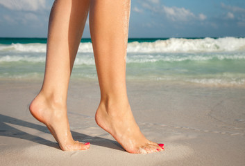 summer vacation and pedicure concept - closeup of woman legs walking on exotic beach sand