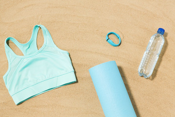 sport, summer and objects concept - sports top, mat, fitness tracker and water bottle on beach sand