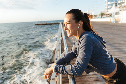 Leinwanddruck Bild Beautiful young sports fitness woman have a rest at the beach outdoors listening music with earphones.
