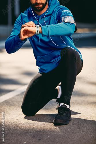 Leinwandbild Motiv Bearded man kneeling on the street and checking heart beat on smart watch. Headphones in ears. Healthy lifestyle concept.