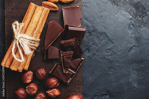 fototapeta na ścianę Chocolate cubes, nuts, dates and cinnamon sticks, healthy eating on a dark background, top view